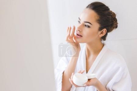 portrait of beautiful woman in bathrobe applying face cream