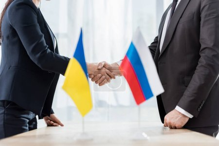 cropped view of diplomats in formal wear shaking hands near ukrainian and russian flags