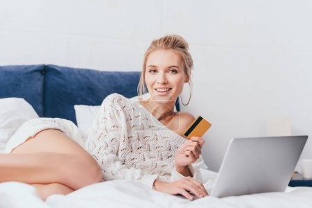 cheerful woman shopping online with laptop and credit card on bed in morning