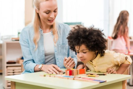 Selective focus of african american kid playing educational game with teacher in montessori school
