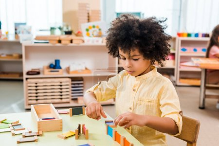Selective focus of african american kid playing educational game at table in montessori school