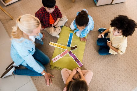 Overhead view of teacher playing with kids educational game on floor in montessori class