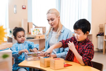 Selective focus of kids playing educational games by teacher in montessori school