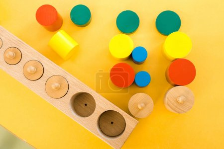 Top view of colorful educational games on yellow desk in class
