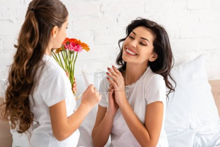 happy woman looking at daughter holding flowers and mothers day card