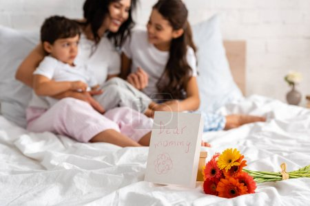 selective focus of happy mother hugging adorable children while sitting in bed near bouquet and mothers day card with dear mommy lettering