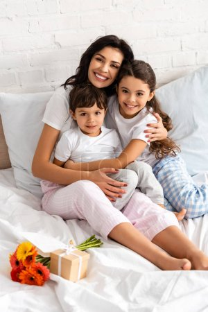 happy mother hugging adorable children while sitting in bed near bouquet and mothers day gift