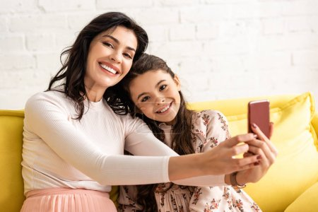 happy mother and daughter smiling at camera while taking selfie on mothers day