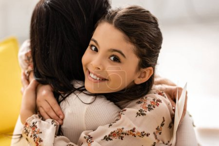 adorable, happy child smiling at camera while embracing mom on mothers day