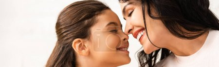 panoramic shot of happy mom and daughter smiling face to face with closed eyes on mothers day