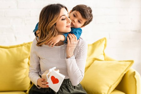cute boy hugging happy mother holding gift box and mothers day card with heart symbol
