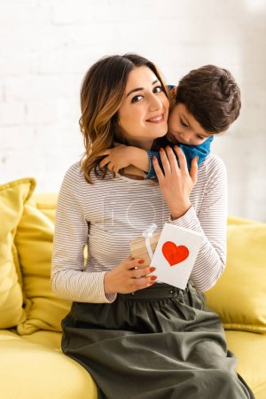 happy woman looking at camera while holding gift box and mothers day card with heart symbol, while adorable son embracing her