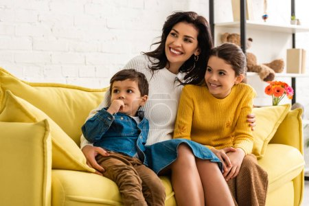 happy mother with son and daughter smiling and looking away while sitting on yellow sofa on mothers day