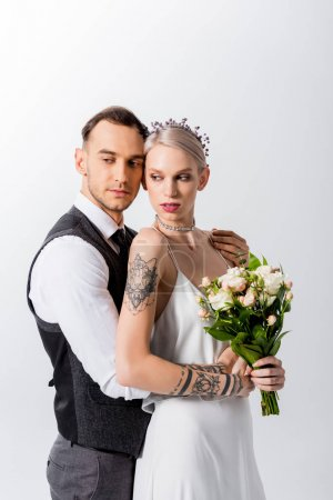 beautiful tattooed bride and handsome bridegroom hugging and looking away isolated on white
