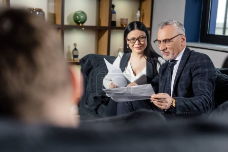 selective focus of smiling businessman and asian businesswoman doing paperwork and talking with man