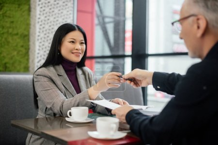 selective focus of smiling asian businesswoman taking pen from businessman in cafe