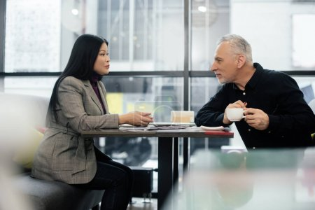 side view of businessman and asian businesswoman talking in cafe