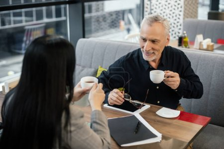 selective focus of smiling businessman holding cup and talking with businesswoman in cafe