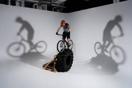 young trial biker in helmet balancing on tractor wheel