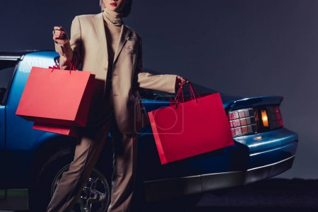 cropped view of woman in suit standing near retro car and holding shopping bags
