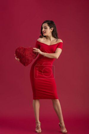 sexy, elegant girl holding decorative heart and smiling while standing on red background