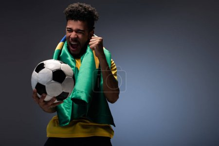 cheerful african american man with brazilian flag shouting and holding football ball on grey