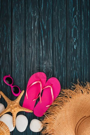 Top view of pink flip flops near sunglasses, starfish and sea stones on dark wooden background