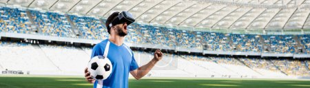 professional soccer player in vr headset with ball yelling and showing yes gesture at stadium, panoramic shot
