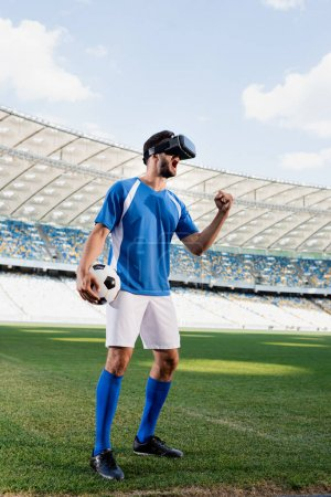professional soccer player in vr headset and blue and white uniform with ball yelling and showing yes gesture on football pitch at stadium