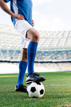cropped view of professional soccer player in blue and white uniform with ball and hands on hips on football pitch at stadium
