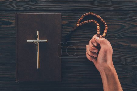 cropped image of man holding rosary in hand