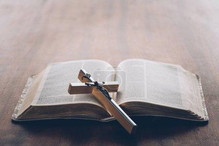 christian cross on open holy bible
