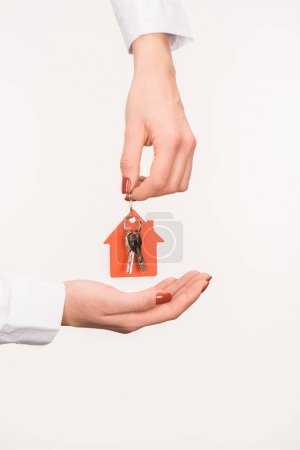 cropped image of female hands holding key from house isolated on white
