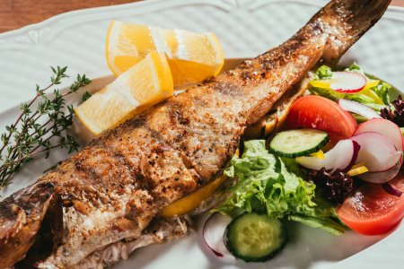 Baked fish with lemon and herbs on white plate with salad