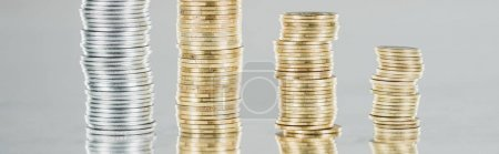 panoramic shot of stacked silver and golden coins on surface with reflection isolated on grey