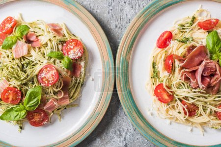 top view of cooked Pappardelle with tomatoes, basil and prosciutto on plates on grey surface