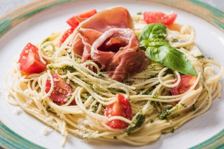 close up view of cooked Pappardelle with tomatoes, basil and prosciutto