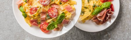 selective focus of cooked Pappardelle with tomatoes, basil and prosciutto on plates on grey surface, panoramic shot
