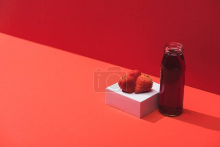 fresh berry juice in glass bottle near ripe strawberries on cube on red background