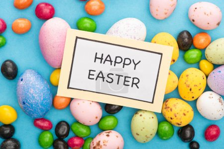 Top view of card with happy easter lettering on colorful chicken and quail eggs, candies on blue background