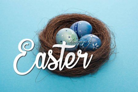 Close up view of Easter eggs in nest on blue with happy Easter illustration