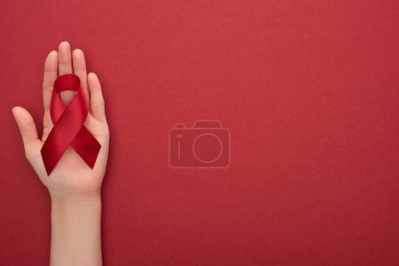 cropped view of woman holding red awareness aids ribbon on red background