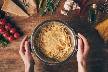 top view of hands with spaghetti pasta and ingredients on wooden tabletop