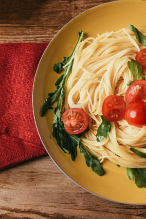 top view of traditional italian pasta with tomatoes and arugula in plate