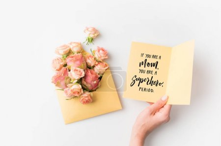hand holding paper with mothers day phrase beside pink flowers in envelope isolated on white