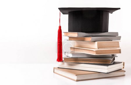 Square academic hat on stack of different books isolated on white