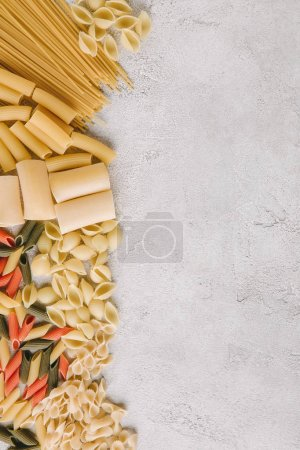 top view of different raw pasta spilled on concrete surface
