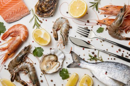 Raw fish and assorted seafood with herbs and lemons isolated on white