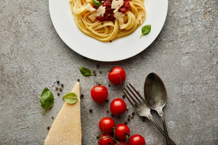 top view of delicious spaghetti with tomato sauce on plate near cheese, tomatoes and cutlery on grey textured surface