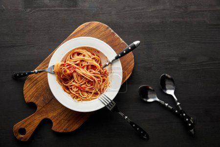 top view of tasty bolognese pasta with tomato sauce in white plate on wooden cutting board near cutlery on black wooden background